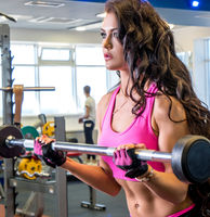 In fitness room. Beautiful woman lifting weight