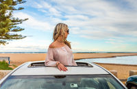 Road trip summer beach vibes.  Carefree woman in sunroof car by beach