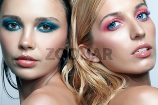 Closeup shot of blonde and brunette girls. Female friendship concept