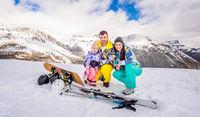 Happy family on ski and snowboard holidays, Livigno, Italy, Alps