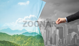 hand pulling green cityscape curtain to gray cityscape