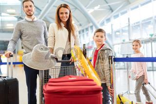 Glückliche Familie mit Kindern und Gepäck