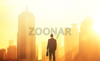 Young smart businessman looking at large city center. Concept of success and appreciation. Standing in front of the spectacular skyline with crowded corporate skyscrapers.