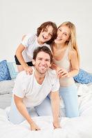 Eltern und Sohn machen Unfug zusammen im Bett