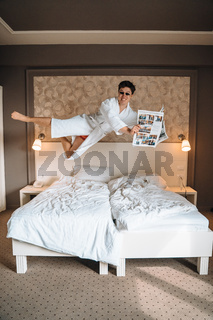 Guy with sunglasses and newspaper high in air.