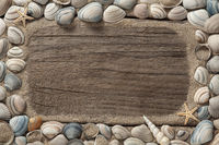 frame, background - sea shells and sand with copy space on weathered wood