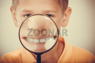 Little boy kid with magnifying glass.