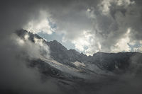 Mountain landscape of a high mountain slope with a cracked glacier muddy volcanic slope against the backdrop of the Caucasus Mountains in the window of clouds. Glaciers of the North Caucasus