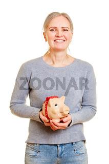 Seniorin hält Sparschwein in den Händen