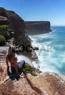 Woman watches waterfall flows off cliffs into ocean