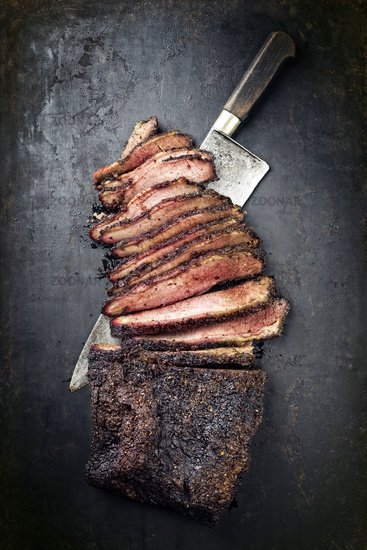 Traditional smoked barbecue wagyu beef brisket offered as top view with knife on an old rustic board with copy space