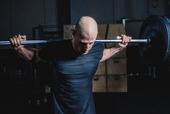 Athletic Muscular Man Holding Barbell On Your Shoulders In Gym. Dramatic Color Grading.