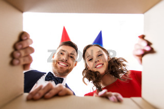 couple in party hats opening birthday gift box