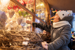 girl choosing christmas decorations at market