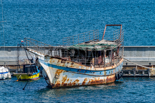Old rusted Fishing Boat docked at a harbor port in Nessebar ancient city on the Bulgarian Black Sea Coast. Old fishing boat with rust docked at a harbor port