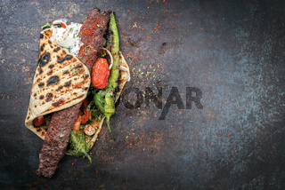 Traditional Adana kebap on a skewer with tomato and yogurt on a flatbread with copy space right