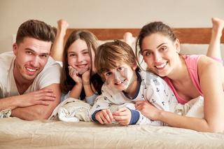 Glückliche Eltern mit zwei Kindern im Schlafanzug