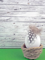 Easter background with Easter egg isolated on green in front of wood