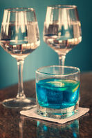 Long drink with blue curacao and two glasses of rosé wine