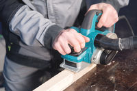 Close-up of a carpenter's hand working with an electric plane with suction of sawdust. Leveling and sanding wooden bars