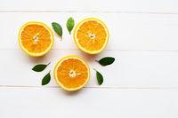 Fresh orange citrus fruit with leaves on white wooden