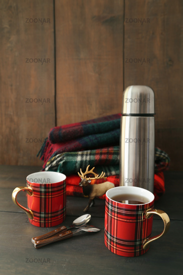 Mugs with hot tea and thermos