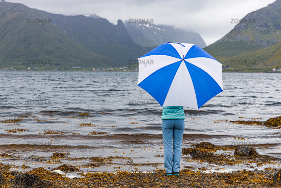 Woman under an umbrella in the background of nature Norway