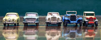 a line of retro toy cars parked on a old wooden floor