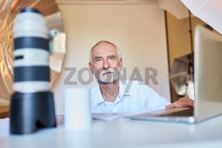 Fotograf am Laptop Computer bei Bildbearbeitung