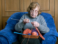grandmother knits with knittings in a room sitting