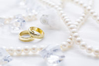 Two golden rings with pearl necklace and on white background as symbol of love and marriage