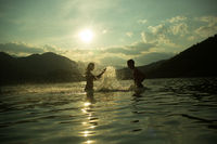 Silhoueted young couple at the beach on a hazy summer day at dusk,  enjoying splashing in the ocean water, getting wet,