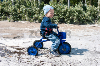 A blond-haired boy in blue rides a small tricycle in a puddle completely covered with the old fluffy poplar fluff