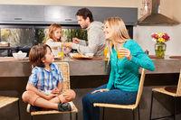 Familie beim gemeinsamen Frühstück in Küche
