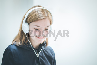 Young cute girl is listening to music with headphones