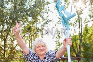 Seniorin mit Krücken freut sich über die Genesung
