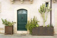 Façade of typical town house with green cactuses and old door in a Mediterranean city (Syracuse) on