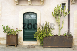 Façade of typical town house with green cactuses and old door in a Mediterranean city (Syracuse) on Sicily