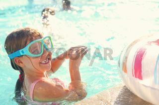 One small girl having fun in outdoor pool