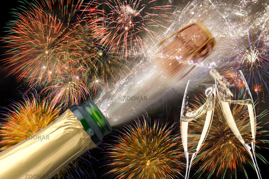 splashing bottle of champagne with flying cork and firework at Silvester 2019