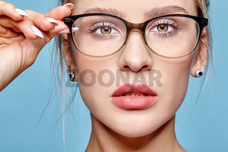 Portrait of attractive young woman in glasses on blue background