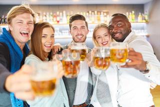 Lachende Gruppe Freunde beim Bier trinken