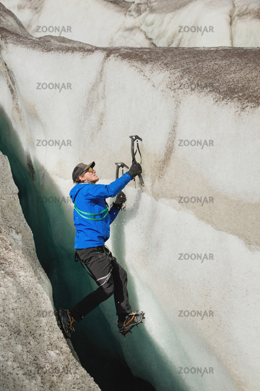 A free climber without insurance with two ice axes rises from a crack in the glacier. Free climbing without ropes