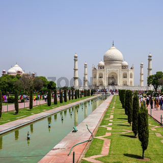 View on Taj Mahal with walkway, garden square, reflecting pool and visitors. UNESCO World Heritage in Agra, Uttar Pradesh, India