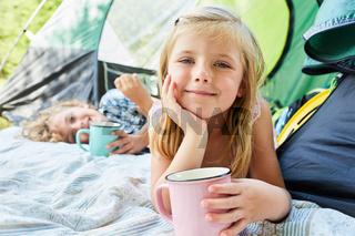 Mädchen mit einer Tasse vor dem Zelt