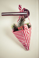 Small Christmas bag with branch and candy cane hanging on door handle in vintage style