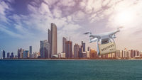 Drone with package flying in front of Abu Dhabi Skyline
