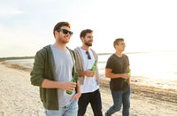young men with non alcoholic beer walking on beach