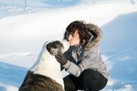 woman kisses a dog on a sunny winter day