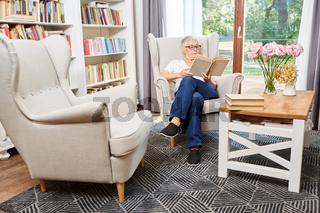 Seniorin liest konzentriert in einem Buch